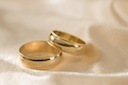 Two golden wedding rings lying by each other cv