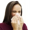 Woman with a cold sneezing into a tissue cv