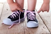 14258141 child successfully ties shoes  closeup on feet and hands cv